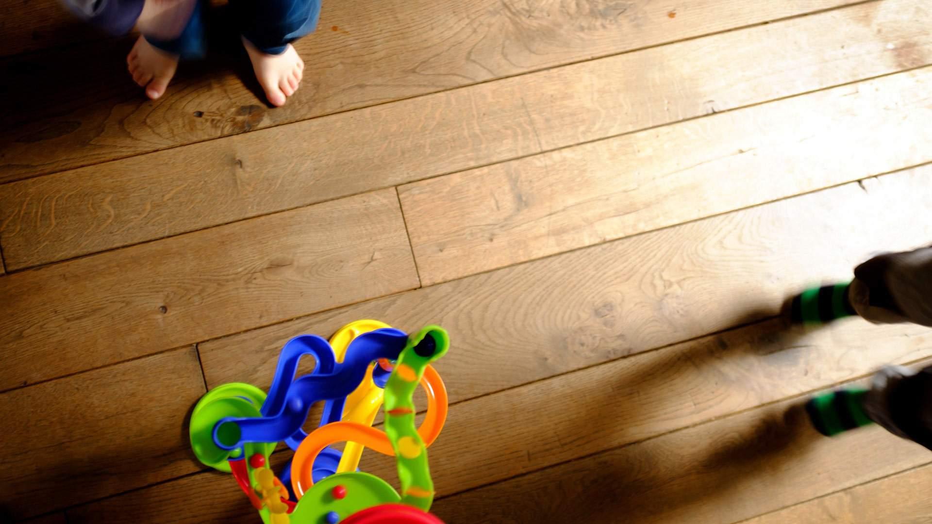 Kinder spielen auf Holzboden