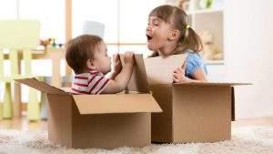 Kinder spielen in Kartons