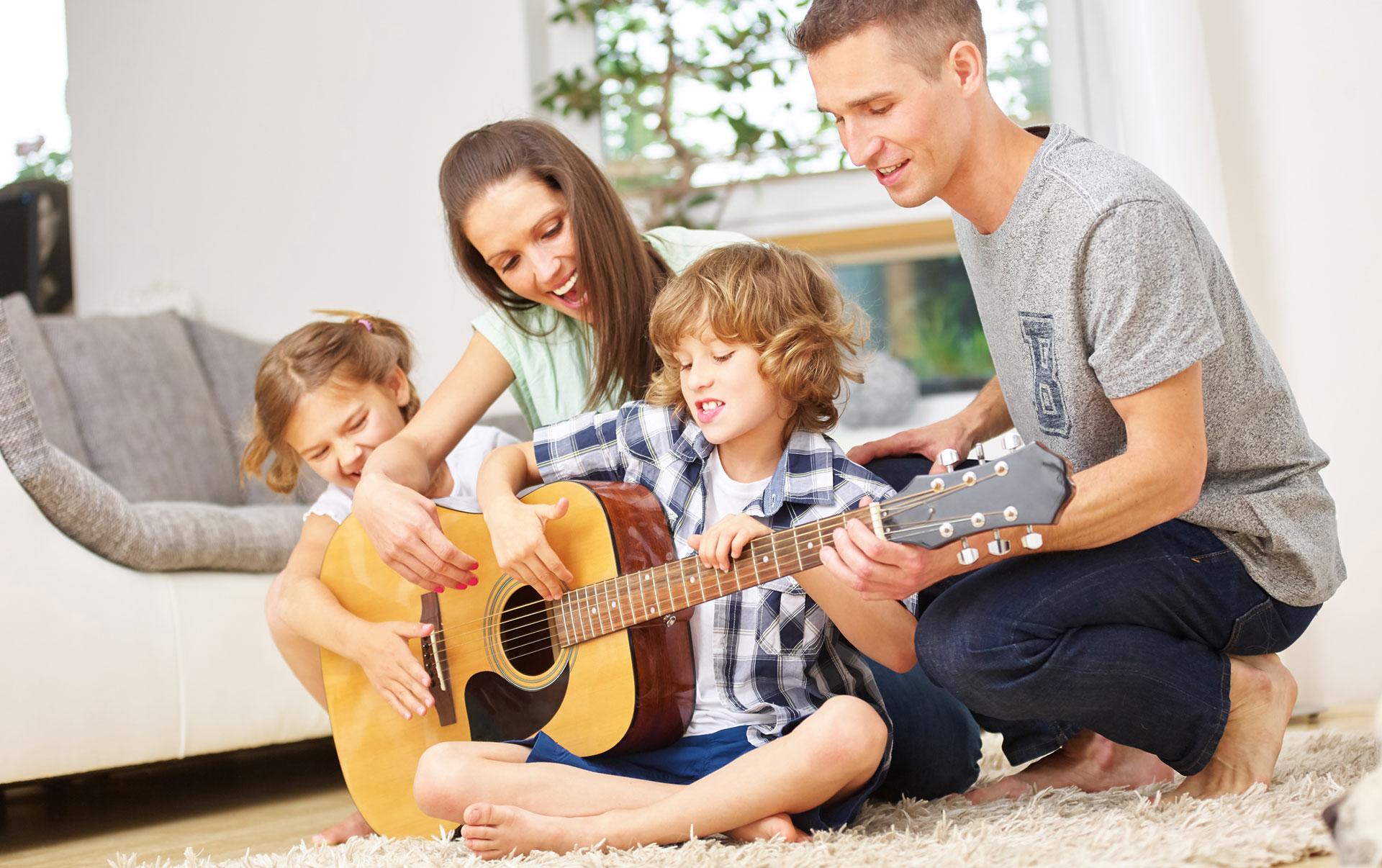 Junge Familie mit Kindern beim Gitarrespielen