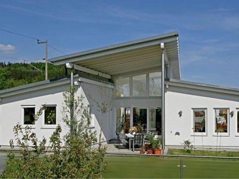 Aussenansicht auf die Hausrückseite und die großzügig überdachte Terrasse.