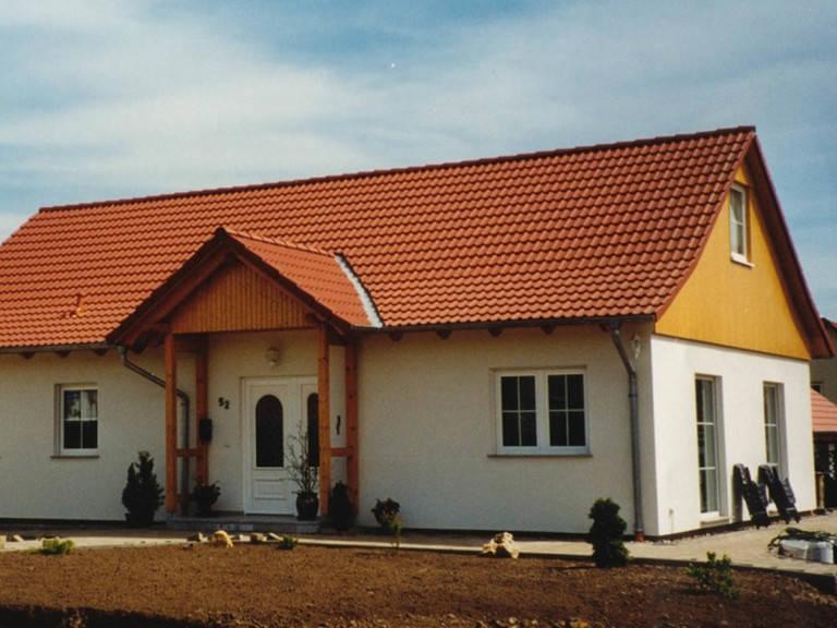 Aussenansicht auf das Satteldachhaus mit überdachtem Hauseingang.