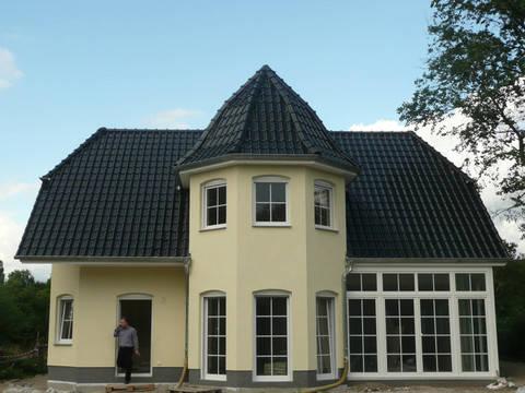 Aussenanansicht auf die Hausrückseite und die große Fensterfront im Wohn- und Essbereich.