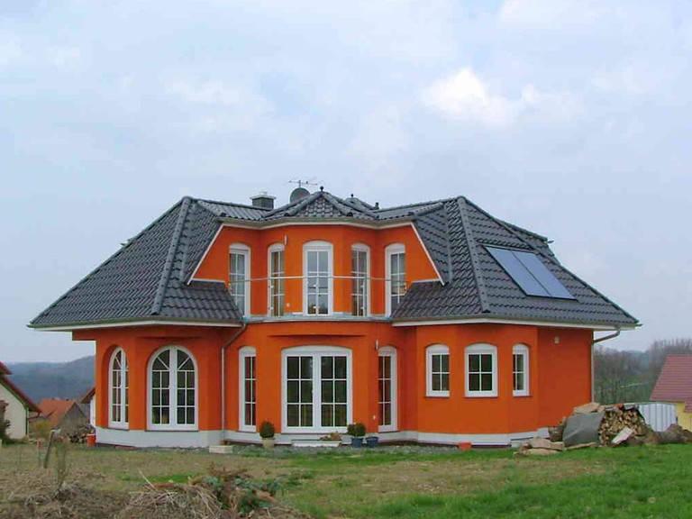 Aussenansicht auf die Hausrückseite mit roter Putzfassade.