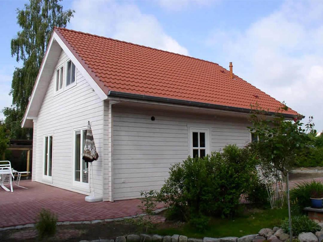 Aussenansicht auf die Terrassenseite des Blockhauses mit Satteldach.