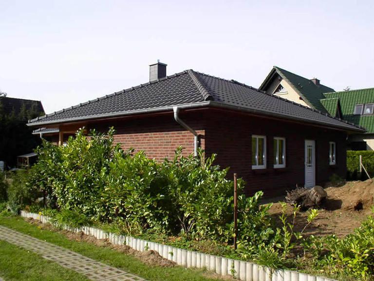 Aussenansicht von der Seite auf den Hauseingang des Bungalows mit Verblendfassade.