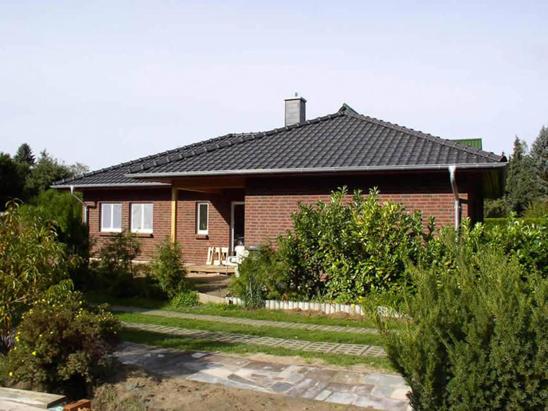Aussenansicht auf die teilweise überdachte Terrasse des Winkelbungalows mit Verblendfassade.