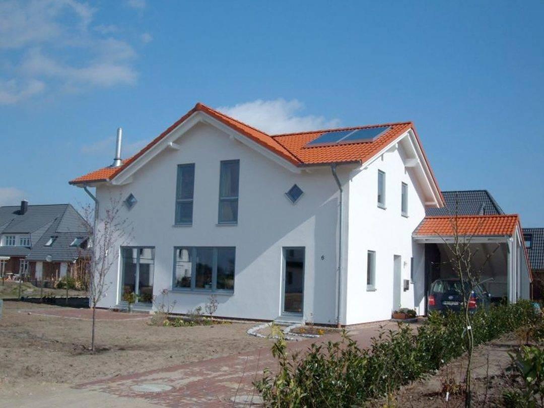 Aussenansicht auf die Terrassenseite des Zwerchdachhauses mit seitlichem Hauseingang.