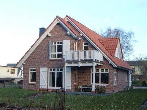 Aussenansicht auf die teilweise überdachte Terrasse und den Balkon im Dachgeschoss.