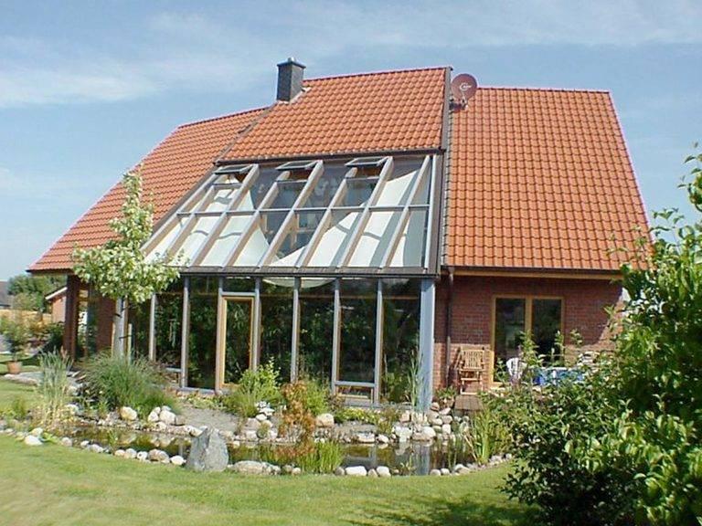 Aussenansicht auf den großen verglasten Wintergarten und die Terrasse.