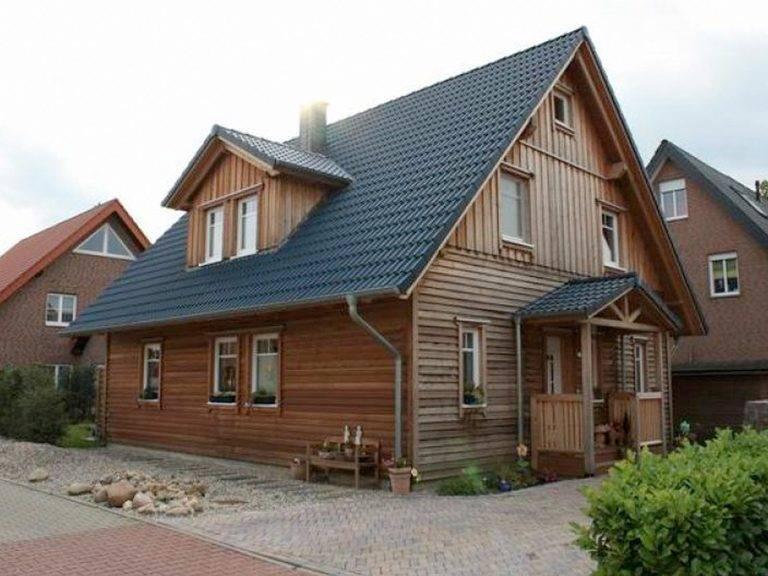Aussenansicht auf den überdachten Hauseingang und die Holzfassade.