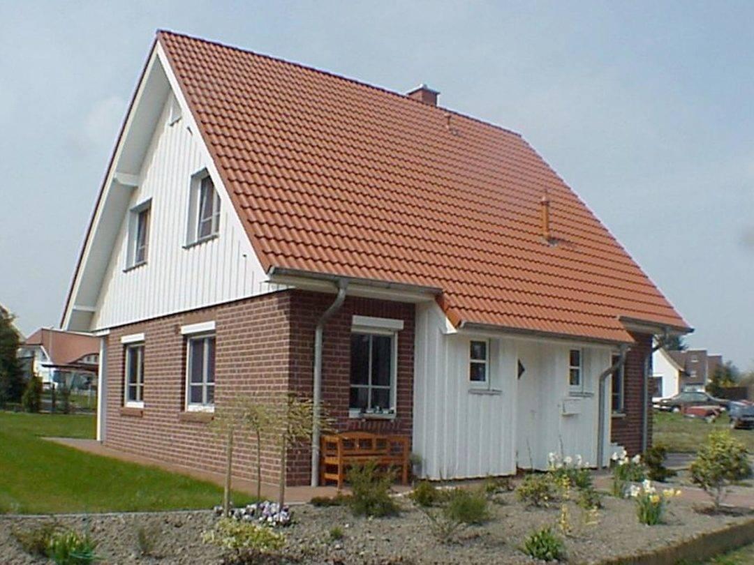 Aussenansicht auf den überdachten Hauseingang des Satteldachhauses.