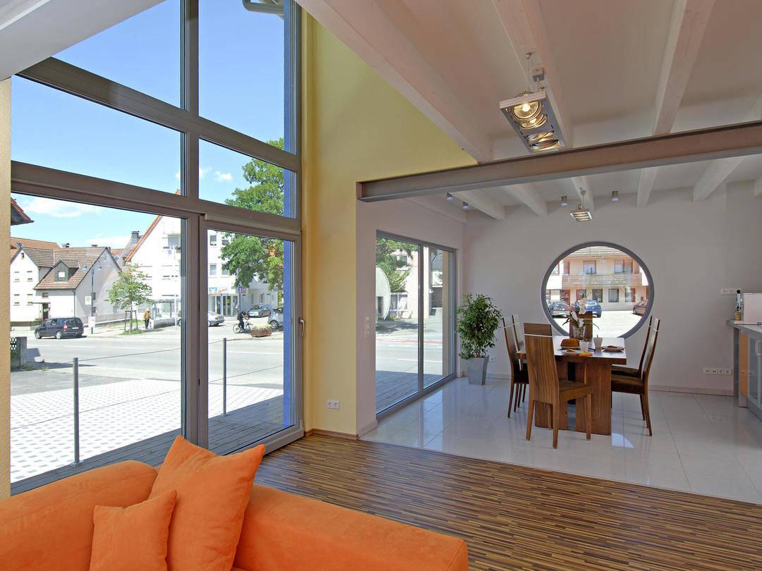Innenansicht durch den Wohnbereich auf die großen Terrassenfenster.
