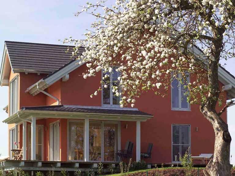 Individuell geplantes Kundenhaus - WOLF System Haus Gartenansicht mit Terrasse