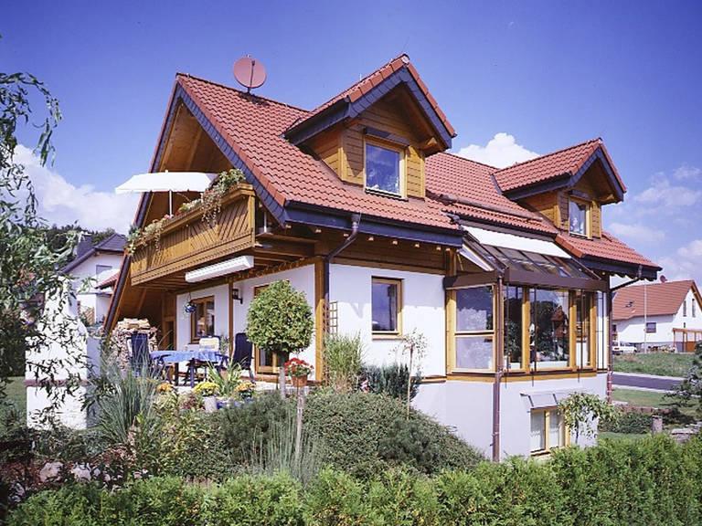 Aussenansicht von der Seite mit Blick auf die Terrasse, den Holzbalkon und die Gaube im Erdgeschoss.