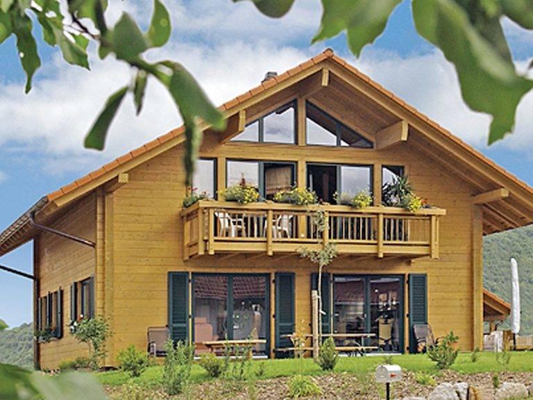 Aussenansicht auf das Holzgaus mit Terrasse und Balkon.