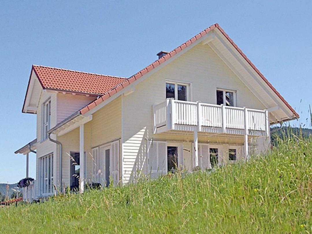 Aussenansicht auf den Balkon und das Zwerchdach des Holzhauses.