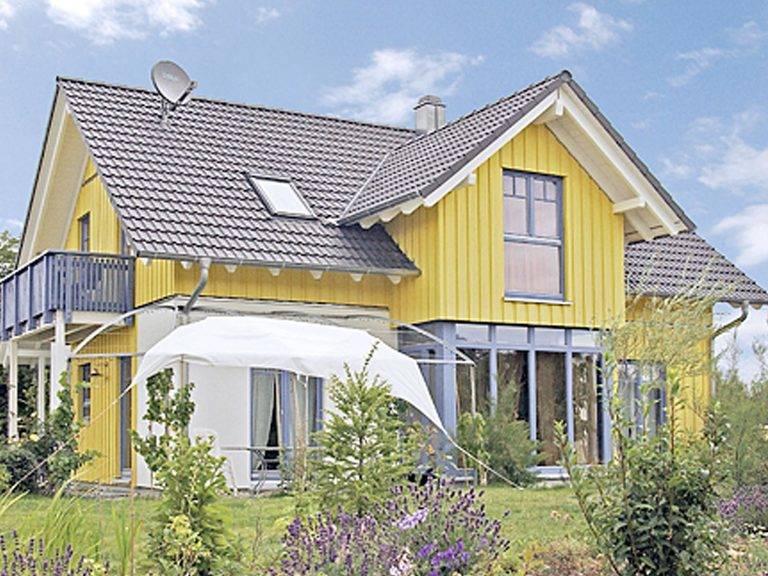 Aussenansicht auf das Zwerchdachhaus mit Wintergarten und Terrasse.