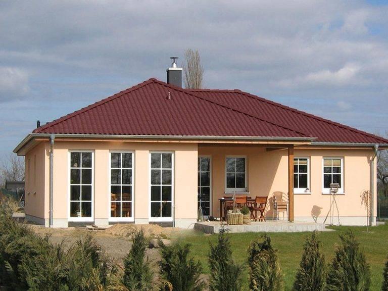 Aussenansicht auf die Hausrckseite mit Terrasse und bodentiefen Sprossenfenstern.