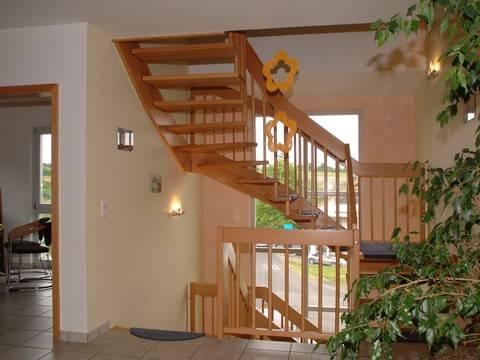 Innenansicht auf die offene Holztreppe und den großen Flur.